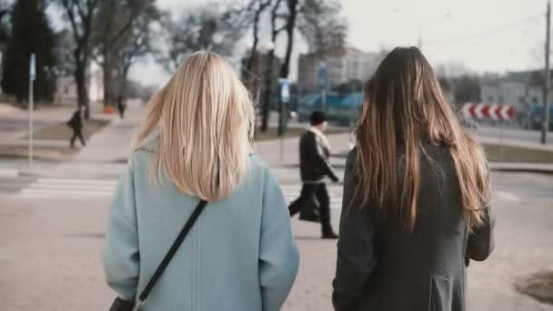 Dvě kamarádky společně chůzi na ulici. Mladé dámy v elegantní stylové oblečení v městské prostředí. Pohled zezadu