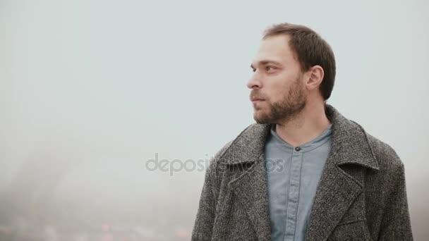 Nachdenklicher junger Mann steht in der Innenstadt, am nebligen Morgen in der Nähe des Eiffelturms in Paris, Frankreich und schaut sich um.