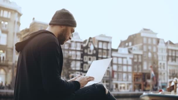 Ufficio K : Uomo creativo k che si siede con il computer portatile in strada