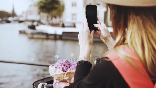 Female with bicycle takes photos on river bridge. Lady with long hair and flowers shares photos with friends online. 4K