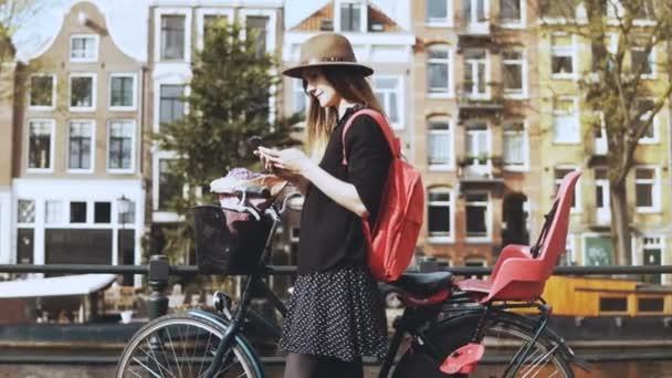 Krásná žena s smartphone na mostě a jízdních kol. Módní blogger psaní zpráv na malebném mostu. Životní styl. 4k