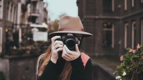 Portrait of happy Caucasian woman with a camera. Attractive cheerful lady in stylish hat taking a picture 4K front view.