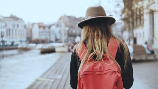 Touristinnen spazieren, fotografieren am Flussufer. Mädchen mit langen Haaren, rotem Rucksack verschickt Bilder an Freunde im Internet. 4k
