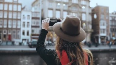 Tourist lady takes photos of old architecture. Girl with long hair and red backpack enjoying amazing city scenery. 4K.