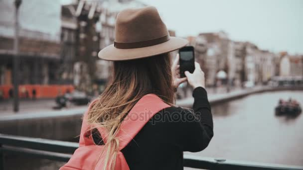 Young girl in hat takes photos of scenic river. Girl with long hair and red backpack sharing pictures on her blog. 4K.