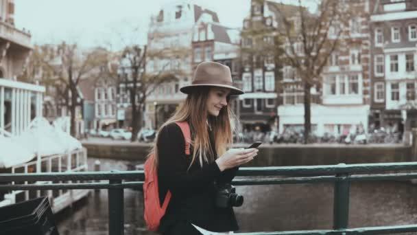 Krásná žena používá sociální sítě na smartphone. 4 k. dospělých 30s Evropská žena s dlouhými vlasy v klobouku napíše zprávu.