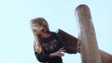 Cute little girl having fun in adventure park. Pretty happy smiling child female hesitating, worried on ropes course.