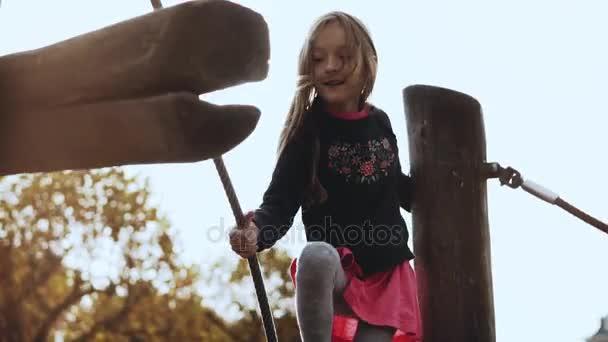 Porträt eines kleinen entzückenden Mädchens auf dem Spielplatz. Nettes lächelndes 6-jähriges Mädchen geht fröhlich über Hindernisse auf Showgelände.