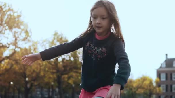 Portrét předškolní dívky v parku dobrodružství. Roztomilý šťastné dítě s dlouhými vlasy prochází lana kurzu překážek