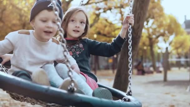 Two Caucasian children on a swing in autumn park. Happy kids friends swinging together on a peaceful sunny fall day.