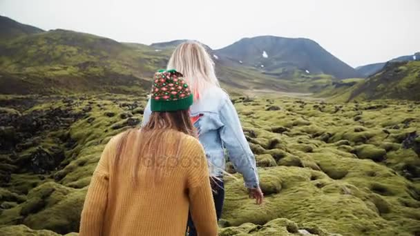 Two tourists woman walking through the lava field in Iceland covered moss. Girls raises hands, feels happy and freedom.