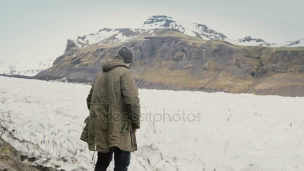 Young handsome man standing on the mountain and looking on glaciers in Vatnajokull ice lagoon in Iceland.
