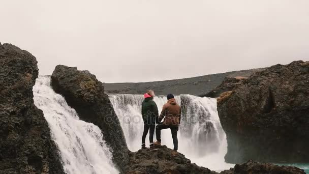 Back view of young couple standing on a rock and looking on a powerful waterfall in Iceland, holding hands.