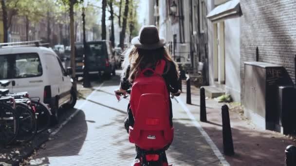Pohled zezadu. Žena na projížďku na kole sluneční město. Zpomalený pohyb. Dívka v stylové čepice s červeným batohem na kole. Zkoumání
