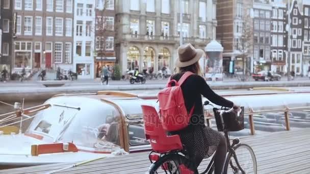 Bloggerin radelt an einem Flusskai entlang. Tourismus. Kaukasisches Mädchen mit Hut auf einem Stadtrad. Seitenansicht Zeitlupe.