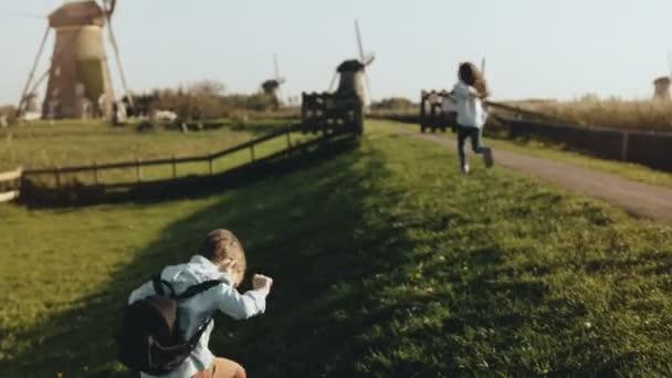 Dvě malé děti si hrají v blízkosti staré windmill farm. Šťastné děti pobíhat rustikální vesnické scenérie. Štěstí a radost. 4k