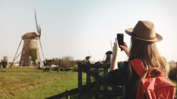 Millennial tourist girl takes a photo of windmill. Traveler woman in hat with red backpack enjoys pastoral scenery. 4K.