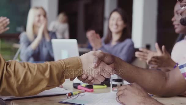 Two partners, african and caucasian businessmen shake hands. Group of people clapping on a background at modern office.