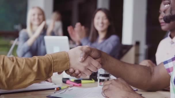 Two partners, african and caucasian businessmen shake hands. Group of people clapping on a background at office. slow mo