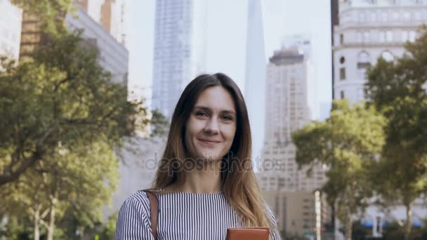 Portrait of young happy businesswoman standing in the park of financial centre of New York, USA and holding documents