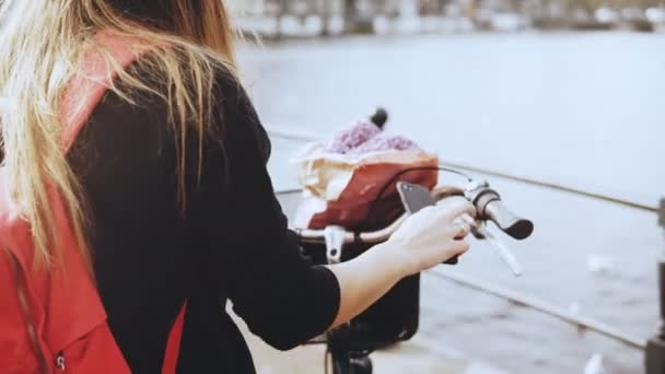 Creative businesswoman takes photos on a bridge. Stylish lady on bicycle photographs beautiful river town scenery. 4K.