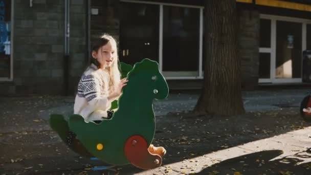 Pretty girl on a green dinosaur spring rider. Happy Caucasian kid excited, talking to parents. Bright sunlight shot. 4K.