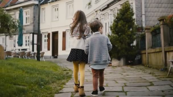 Two little kids walk together near old buildings. Children, girl and boy wander around beautiful German old town. 4K.