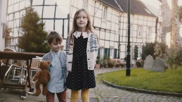 Little girl and boy stand together making faces. European siblings look at camera smiling silly. Half-timbered house 4K.