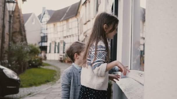 Roztomilý chlapec a dívka vybrat dárky na hračku průčelí. Dvě kavkazské děti stojí okno nakupování. Hattingen, Německo. 4k