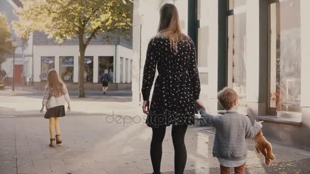 Matka chodí spolu chlapec a dívka. Držení rukou. Žena tráví čas s malými dětmi. Rodinná dovolená. 4k