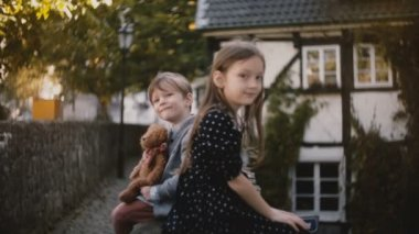 Portrait of little European boy and girl. Brother and sister sit together looking at camera. Half timber houses. 4K.