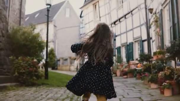 Kamera sleduje malou holčičku běžící na dlážděné silnici. Pohled zezadu. Staré hrázděné domy Hattingen, Německo. 4k