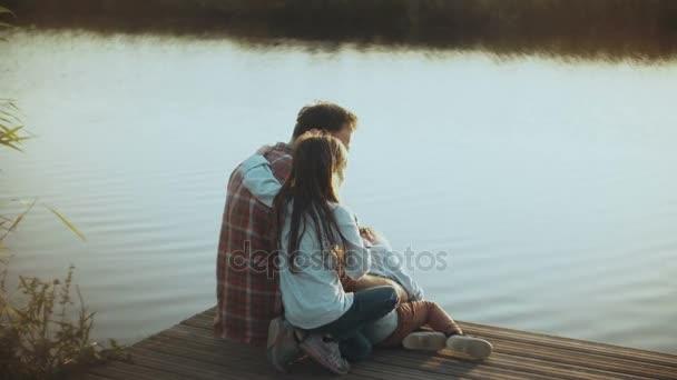 Otec se dvěma dětmi sedí na klidné řeky molo. Evropské rodiny spolu strávit šťastný čas na krásné letní západ slunce. 4k