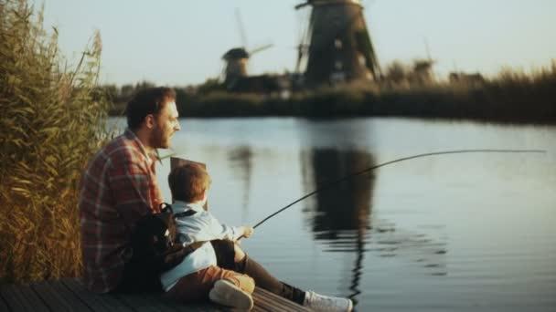 Evropská otec a syn sedět spolu na jezeře molu. Chlapec má ručně vyrobené rybářské náčiní. Šťastné vztahy v rodině. 4k.
