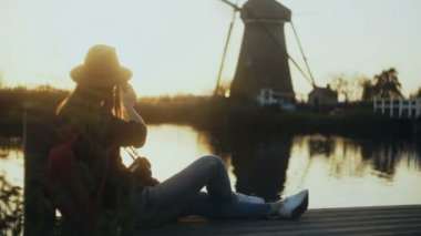 Woman in hat sits on sunset lake pier Netherlands. Female blogger with smartphone and camera takes a windmill photo. 4K.