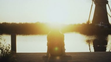 Woman sits on a small lake pier, watching sunset. Golden hour. Perfect moment of peace and inner harmony. 4K back view.