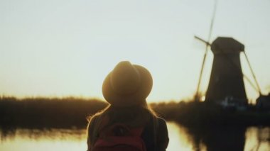 Happy female traveler in hat watches setting sun. Woman smiling on a beautiful lake pier, old wind mill. 4K back view.