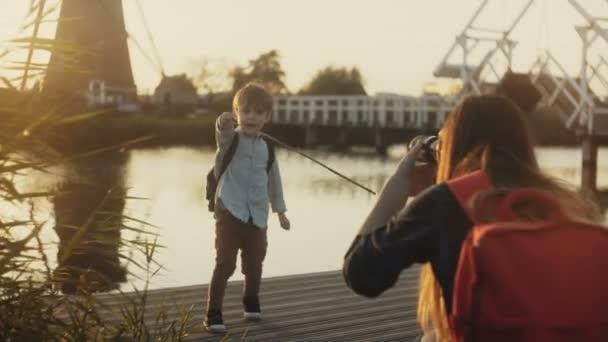 Matka má fotografie chlapce hrát pirátské. Rodinnou zábavu čas na západ jezero molu. Starý větrný mlýn. Malý herec. 4k
