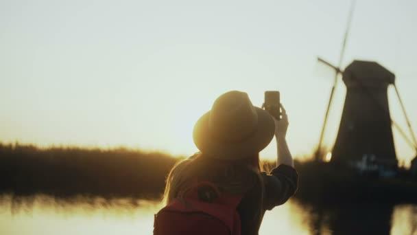 Жінка в капелюсі сидить на захід сонця сільській місцевості озеро ... f646d05843318