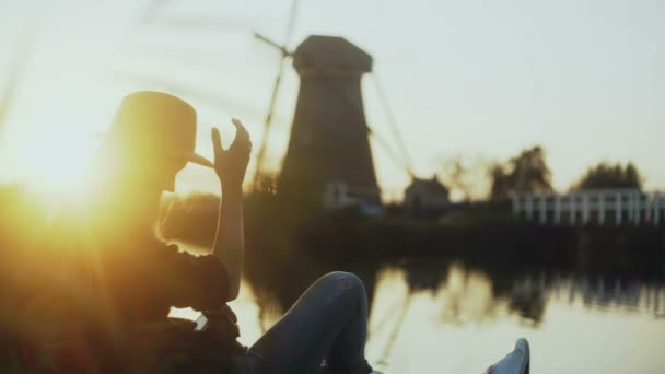 Millennial girl sits with phone on lake pier. Setting sun. Woman using shopping app outdoors. Old Dutch windmill. 4K.