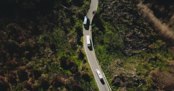 Aerial view of vehicles on a narrow mountain road. Tour bus stops at roadside to let oncoming cars pass. Safety. 4K.