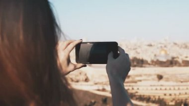 Girl takes smartphone photos of Jerusalem, Israel. Female hands holding phone on a sunny day. Capturing moments. 4K.