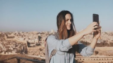 Pretty girl takes selfie in Jerusalem old town. Cute local girl smiles happy, taking photos. Ancient Israel panorama 4K.