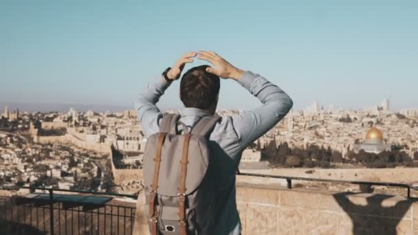 Excited European tourist male raises hands. Israel, Jerusalem. Arms wide open. Man with backpack enjoys amazing view 4K.