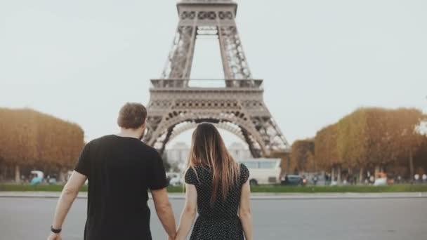Fiatal, boldog pár séta, közel az Eiffel-torony Párizsban. Férfi és nő, átölelve és megcsókolta az utcán.