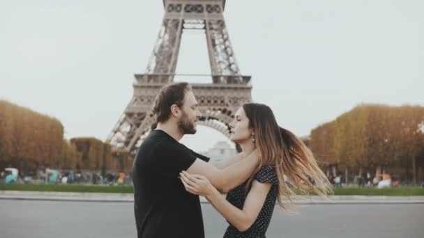 Young happy couple walking, kissing near the Eiffel tower in Paris, France. Traveling man and woman on honeymoon.