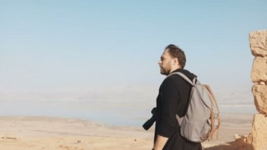 Caucasian man enjoys amazing Dead Sea panorama. Excited photographer stands on mountain top with camera Israel Masada 4K