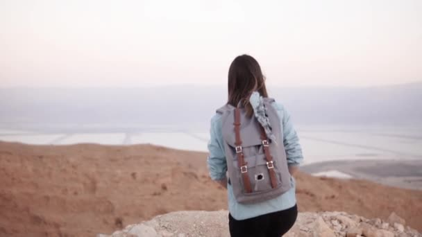 Woman takes photos of montain scenery. Slow motion. Casual traveler girl with backpack using smartphone. Israel Dead Sea