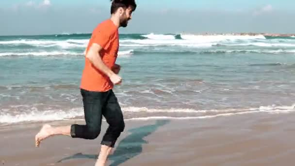 European bearded man running on sea beach. Freedom concept. Male tourist runs barefoot on amazing summer seashore. 4K.