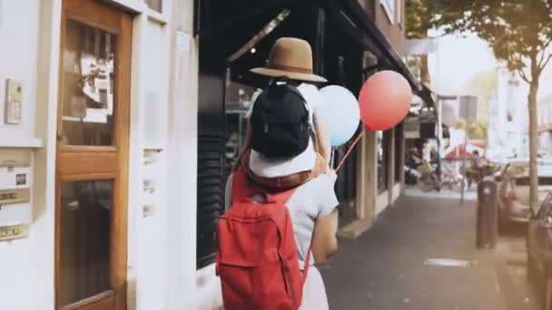 Mother carries son on shoulders along the street. Girl walks with a little happy kid in hat and two air balloons. 4K.